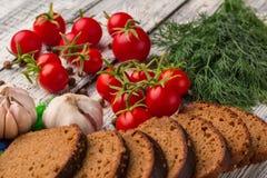 Stilleben: tomater svart bröd, vitlök, fänkål, bayberry Royaltyfri Foto
