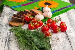 Stilleben: tomater svart bröd, vitlök, fänkål, bayberryfart Arkivfoton