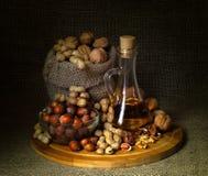 Stilleben; valnötter jordnötter, hasselnötter, valnötolja, på brädet royaltyfri bild