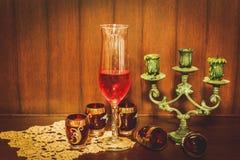Stillebenbild av rött vin och ljusstaken över träbackgro Arkivfoto