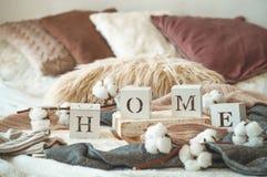 Stillebendetaljer i hemmiljö av vardagsrum och inskriftHEMMET Böcker och kopp te med kotten och bomull läst rest royaltyfri foto