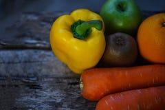 Stillebenfrukt med f?r ?pplemorot f?r gul spansk peppar den gr?na apelsinen och kiwin p? lantligt tr? arkivbild
