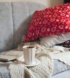Stillebeninredetaljer, kopp te och bok på soffan Arkivfoto