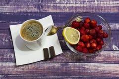 Stillebenkaffe med choklad, jordgubbar och citronen på en härlig bakgrund royaltyfri fotografi