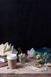Stillebenkaffe som går med kakor, socker och böcker på den trätabellen och svartväggen Santa Claus med påsen av gåvorna kopiera a Royaltyfria Bilder