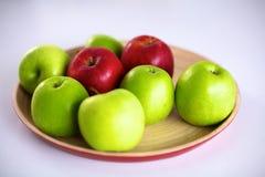 Stillebenordning av äpplen på ett träuppläggningsfat Fotografering för Bildbyråer