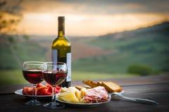 Stillebenrött vin, ost och prosciutto arkivfoton