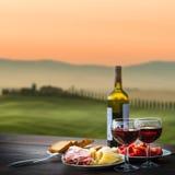 Stillebenrött vin, ost och prosciutto arkivbild
