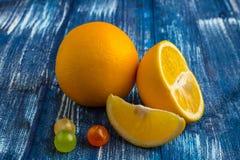 Stillebensammansättning av apelsiner och godisar på blå bakgrund Royaltyfri Bild