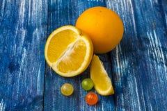 Stillebensammansättning av apelsiner och godisar på blått trä Arkivbilder