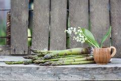 Stillebensammansättning med sparris och den keramiska krukan med liljekonvaljen blommar Arkivbilder