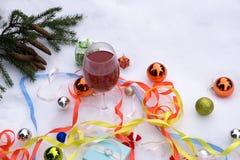 Stillebenvin, gåvor och julgranprydnader i snön Arkivbilder