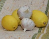 Stillebenvitlök och citroner på tekstilnoy yttersida Royaltyfria Foton