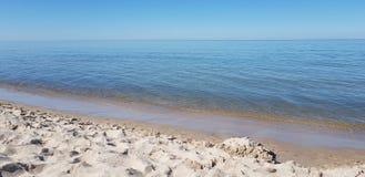 Stilles haarscharfes Wasser der Seeküste Stockbild