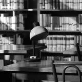 Stilleven in een oude bibliotheek met een lamp op een lijst stock afbeeldingen