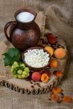 Stilleven in een rustieke stijl: kwark in een een kleischotel, melk en vruchten op houten achtergrond Stock Fotografie