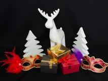 Stilleven, giftdozen, herten, met Kerstbomen en Carnaval-maskers Op een zwarte achtergrond royalty-vrije stock afbeeldingen