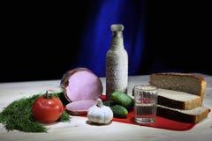 Stilleven met brood, ham, groenten en fles wodka Stock Afbeeldingen