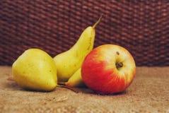 Stilleven met drie peren en één rode appel op een bruine achtergrond stock fotografie