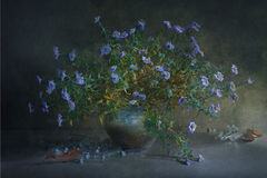 Stilleven met een grote boeket kleine blauwe bloem op takken in een verspreide kleipot en heel wat glas transparante kleine fless Stock Afbeeldingen