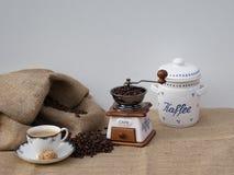 Stilleven met een oude koffiemolen, een kop van koffie en het oude tin van de porseleinkoffie royalty-vrije stock fotografie