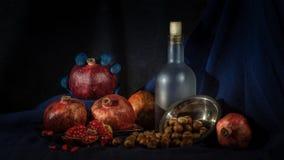 Stilleven met fles, granaatappel en okkernoten op hellouvin royalty-vrije stock afbeelding