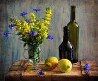 Stilleven met flessen door citroenen en bloemen Royalty-vrije Stock Foto's