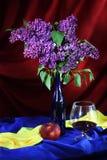 Stilleven met glas van rode wijn, sappige appel en sering in vaas Stock Afbeeldingen