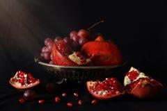 Stilleven met granaatappels en druiven Stock Fotografie