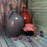 Stilleven met jampot, ceramische botles en pruimen royalty-vrije stock foto