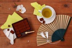 Stilleven met Japanse chocolade, groene thee, en een ventilator op een wo Royalty-vrije Stock Fotografie