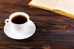 Stilleven met kop van koffie en boek op grunge houten lijst in uitstekende stijl Stock Foto