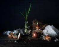 Stilleven met uien op een houten lijst aangaande een donkere achtergrond Stock Afbeeldingen