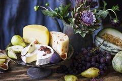 Stilleven met verschillende kaas, verse vruchten en tuinbloemen Royalty-vrije Stock Foto's