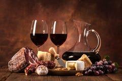Stilleven met wijn, kaas en worsten Stock Foto