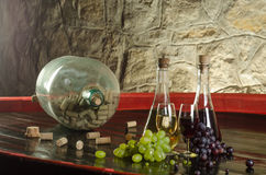 Stilleven met wijnglazen, wijnflessen en druiven in oude kelder Stock Foto