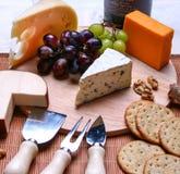 Stilleven 3 types van de kaas van de kaasroquefort, rode en groene druiven, crackers, okkernoten, kaaswerktuigen op houten plaat stock foto's