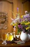 Stilleven van geneeskrachtige kruiden, honing, aftreksel en geneesmiddelen stock afbeeldingen