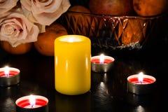 Stilleven van kaarsen van verschillende kleuren, bloemen en vruchten royalty-vrije stock foto
