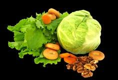 Stilleven van sla, kool, gedroogd fruit, appel, drogen, noten en droge die abrikozen op zwarte achtergrond wordt geïsoleerd stock afbeelding