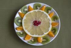Stilleven van vruchten in een witte plaat op een groene achtergrond stock foto