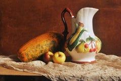 Stillevenfoto van kruik met vruchten het snijden en twee appelenom houten achtergrond Stock Foto