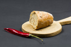 Stillevensamenstelling met houten keuken scherpe raad, brood en Spaanse peper Stock Afbeelding