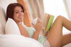 Stillgestandener Mädchengetränk-Morgenkaffee und gelesenes interessantes Buch Stockbild