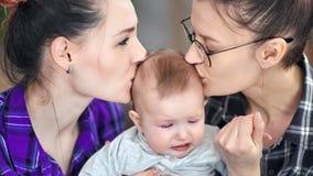 Stillhet för den kvinnliga föräldern för närbild som två behandla som ett barn försökande ner gråter rubbning lite, att kyssa och