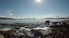Stillhet vinkar slå den steniga kusten i ljust vårsolsken med klar blå himmel arkivfilmer