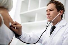Stillhetdoktor som sätter stetoskopet på baksidan av hans patient fotografering för bildbyråer