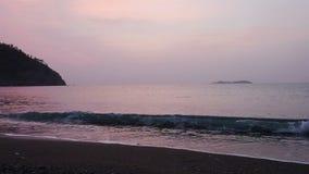 Stillhetvågor av havet på den sandiga stranden på solnedgången Solreflexion i havsvatten mot bakgrund field blåa oklarheter för g stock video