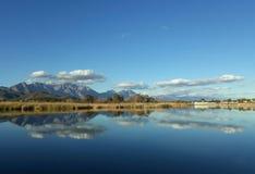 Stillhetvatten och reflekterande vatten som visar moln med bakgrunden av berg Arkivbilder