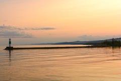 Stillhetvatten på solnedgången på en hamnvågbrytare Royaltyfria Bilder